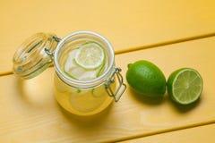 Λεμονάδα με τον πάγο, το λεμόνι και τον ασβέστη σε ένα βάζο σε ένα κίτρινο ξύλινο BA Στοκ Εικόνες