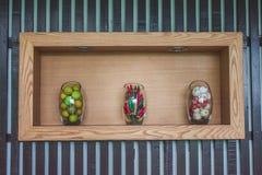 Λεμόνια λαχανικών, τσίλι, σκόρδο στο βάζο γυαλιού στο ξύλινο ράφι στοκ εικόνες με δικαίωμα ελεύθερης χρήσης