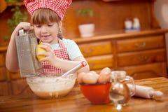 Λεμόνια μηχανών πλανίσματος λίγων αστεία κοριτσιών στην κουζίνα Στοκ εικόνα με δικαίωμα ελεύθερης χρήσης