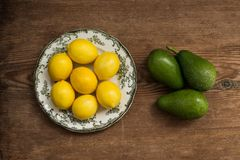 Λεμόνια στο άσπρο πιάτο και αβοκάντο πέρα από το αγροτικό υπόβαθρο Στοκ Εικόνες