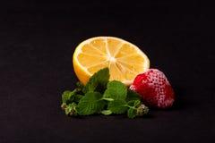 Λεμόνι, παγωμένες φράουλες και μέντα στο μαύρο υπόβαθρο Στοκ Φωτογραφίες