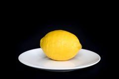 Λεμόνι σε ένα άσπρο πιάτο Στοκ φωτογραφία με δικαίωμα ελεύθερης χρήσης