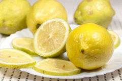Λεμόνι στο άσπρο πιάτο εκτός από το μισό κομμάτι και τις φέτες Στοκ Εικόνες