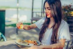 Λεμόνι συμπιέσεων γυναικών στη μερίδα των ψαριών σε ένα εστιατόριο Στοκ φωτογραφία με δικαίωμα ελεύθερης χρήσης