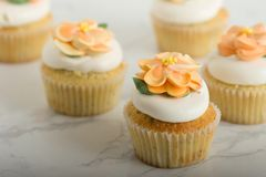 Λεμόνι Cupcakes με τα λουλούδια Buttercream στο μαρμάρινο πίνακα στοκ εικόνες