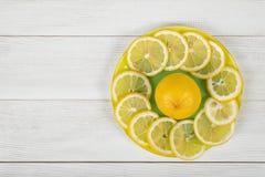 Λεμόνι peaces που σχεδιάζεται γύρω από ολόκληρο το λεμόνι σε ένα πιατάκι Στοκ εικόνα με δικαίωμα ελεύθερης χρήσης
