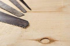 Λεπίδες διάφορων πριονιών που βρίσκονται σε ένα φύλλο του κοντραπλακέ Στοκ Εικόνες