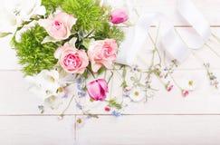 Λεπτά άσπρα, μπλε, ρόδινα λουλούδια και άσπρη κορδέλλα στο λευκό ξύλινο πίνακα Η υπερυψωμένη τοπ άποψη, επίπεδη βάζει διάστημα αν Στοκ Φωτογραφία