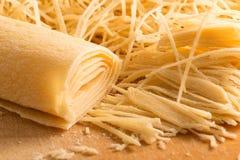 Noodles περικοπών χεριών στον ξύλινο τέμνοντα πίνακα Στοκ Φωτογραφία