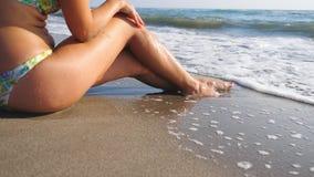 Λεπτά πόδια γυναίκας ξαπλωμένη στην τροπική παραλία και απολαμβάνει διακοπές Κύματα θερμού ωκεανού που πλένουν δεμένα γυναικεία π φιλμ μικρού μήκους