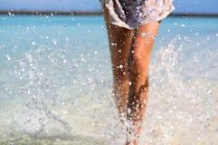 Λεπτά πόδια γυναικών μαυρίσματος που κάνουν τον παφλασμό νερού Διάθεση διακοπών και καλοκαιριού Στοκ εικόνα με δικαίωμα ελεύθερης χρήσης
