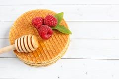 Λεπτές βελγικές βάφλες με το μέλι και τα σμέουρα Λουλούδια της Jasmine και ένα βάζο του μελιού σε ένα ελαφρύ ξύλινο υπόβαθρο Στοκ Εικόνα