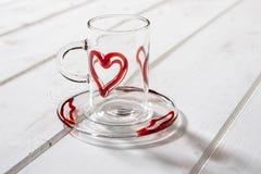 Λεπτές κόκκινες καρδιές κουπών και πιατακιών κρυστάλλου στην ξύλινη επιτροπή Στοκ Φωτογραφίες