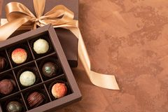 Λεπτές σοκολάτες στο κιβώτιο τεχνών με την κορδέλλα σατέν σε ένα σκοτεινό υπόβαθρο Θέση για το σχέδιο Επίπεδο σχεδιάγραμμα Εορτασ στοκ φωτογραφία