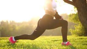 Λεπτή αθλητική γυναίκα που επιλύει στο πάρκο που κάνει την άσκηση ή lunges γόνατο-αναπήδησης Τα πόδια ηλιοβασιλέματος κλείνουν επ απόθεμα βίντεο