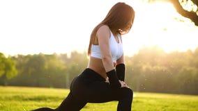 Λεπτή αθλητική γυναίκα που επιλύει στο πάρκο που κάνει την άσκηση ή lunges γόνατο-αναπήδησης Τα πόδια ηλιοβασιλέματος κλείνουν επ φιλμ μικρού μήκους
