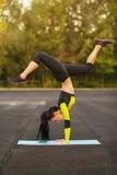Λεπτή αθλητική γυναίκα που κάνει την άσκηση handstand στο στάδιο, φίλαθλο κορίτσι workout, υπαίθρια Στοκ Φωτογραφία
