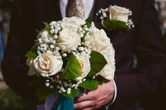 Λεπτή ανθοδέσμη των άσπρων τριαντάφυλλων στα χέρια του νεόνυμφου στοκ εικόνες