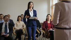 Λεπτή γυναίκα με την ταμπλέτα που υποβάλλει τον ομιλητή μια ερώτηση φιλμ μικρού μήκους