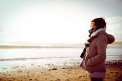 Λεπτή γυναίκα που εξετάζει τη θάλασσα κατά τη διάρκεια του ηλιοβασιλέματος Στοκ εικόνες με δικαίωμα ελεύθερης χρήσης