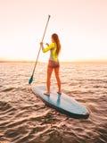 Λεπτή γυναίκα που επιπλέει στη στάση επάνω στον πίνακα κουπιών στη θάλασσα με τα θερμά χρώματα ηλιοβασιλέματος στοκ εικόνες