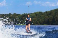 Λεπτή γυναίκα που οδηγά wakeboard στο κύμα της βάρκας Στοκ Εικόνες