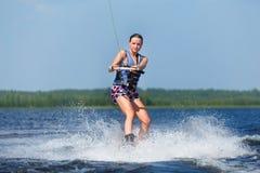 Λεπτή γυναίκα που οδηγά wakeboard στο κύμα της βάρκας Στοκ Εικόνα