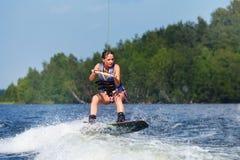Λεπτή γυναίκα brunette που οδηγά wakeboard στη λίμνη Στοκ Φωτογραφίες