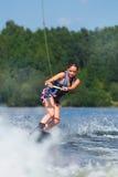 Λεπτή γυναίκα brunette που οδηγά wakeboard στη λίμνη Στοκ Εικόνες