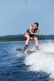 Λεπτή γυναίκα brunette που οδηγά wakeboard motorboat στο κύμα στη λίμνη Στοκ Φωτογραφίες