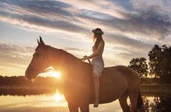 Λεπτή γυναικεία συνεδρίαση σε ένα άλογο και εξέταση το ηλιοβασίλεμα Στοκ εικόνα με δικαίωμα ελεύθερης χρήσης