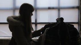 Λεπτή θηλυκή σκιαγραφία που ψάχνει τον εκλεκτής ποιότητας ξεπερασμένο ιματισμό thrift στο κατάστημα απόθεμα βίντεο