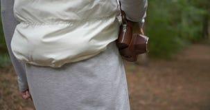 Λεπτή κάμερα holdinga γυναικών σε μια καφετιά περίπτωση στον ώμο της στο δάσος την άνοιξη απόθεμα βίντεο