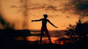 Λεπτή νέα γυναίκα που κάνει τις ασκήσεις ικανότητας στην προθέρμανση στο ηλιοβασίλεμα Εύκαμπτη μορφή, ομαλή κίνηση απόθεμα βίντεο