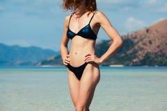 Λεπτή νέα γυναίκα που στέκεται στην τροπική παραλία Στοκ Φωτογραφία