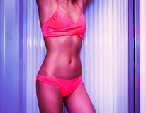 Λεπτή νέα γυναίκα που στέκεται στο σολάρηο που παίρνει suntan στοκ εικόνες με δικαίωμα ελεύθερης χρήσης