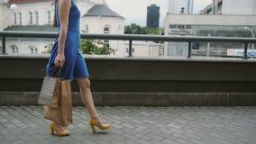 Λεπτή νέα γυναίκα ποδιών, που περπατά στην πόλη κάτω από την οδό με τις τσάντες αγορών, πλάγια όψη, αργό MO, stedicam πυροβολισμό φιλμ μικρού μήκους