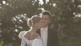 Λεπτή νέα νύφη που περιβάλλει το πάρκο και τα φιλιά απόθεμα βίντεο