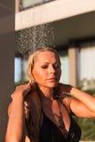 Λεπτή ξανθή γυναίκα που παίρνει το ντους κοντά στη λίμνη υπαίθρια Στοκ Φωτογραφίες