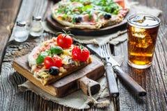 Λεπτή πίτσα φιαγμένη από ζαμπόν, ελιές, arugula και κρύο ποτό Στοκ εικόνα με δικαίωμα ελεύθερης χρήσης