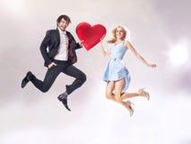 Λεπτή φωτογραφία του εύθυμου ζεύγους που κρατά μια καρδιά Στοκ εικόνες με δικαίωμα ελεύθερης χρήσης