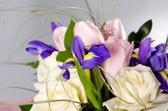 Λεπτή όμορφη ανθοδέσμη της ίριδας, των τριαντάφυλλων και άλλων λουλουδιών στο γκρίζο υπόβαθρο Στοκ εικόνες με δικαίωμα ελεύθερης χρήσης