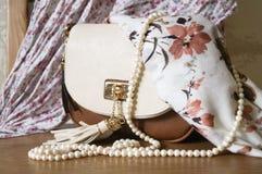 Λεπτοκαμωμένη γυναικεία τσάντα και μια σειρά των μαργαριταριών και του κλωστοϋφαντουργικού προϊόντος στοκ εικόνες με δικαίωμα ελεύθερης χρήσης