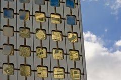 Λεπτομέρεια αρχιτεκτονικής, παράθυρα με τις στρογγυλευμένες γωνίες ενός κτιρίου γραφείων και μπλε ουρανός με τα σύννεφα Στοκ Φωτογραφία