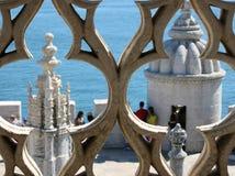 Λεπτομέρεια δύο άσπρων πύργων που βλέπουν μέσω των φυσικών παραθύρων του manuelino Portugense ύφους με εξάλλου τη θάλασσα Λισσαβώ στοκ εικόνες