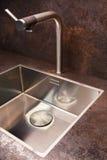 Λεπτομέρεια ενός ορθογώνιου νεροχύτη κουζινών σχεδιαστών με τον κρουνό χρωμίου Στοκ Εικόνες