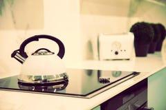 Λεπτομέρεια ενός σφυρίζοντας κατασκευαστή καφέ και μιας φρυγανιέρας σε μια επαγωγή 6 στοκ φωτογραφία
