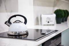Λεπτομέρεια ενός σφυρίζοντας κατασκευαστή καφέ και μιας φρυγανιέρας σε μια επαγωγή στοκ φωτογραφίες