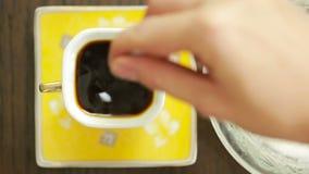 Λεπτομέρεια και κουταλάκι του γλυκού φλυτζανιών καφέ Χύνοντας ζάχαρη στο φλυτζάνι καφέ Τοπ όψη απόθεμα βίντεο
