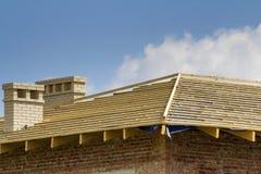 Λεπτομέρεια κινηματογραφήσεων σε πρώτο πλάνο της ξύλινης στέγης του νέου σπιτιού τούβλου με δύο άσπρες καπνοδόχους κάτω από την κ Στοκ φωτογραφία με δικαίωμα ελεύθερης χρήσης